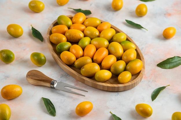 Perto da pilha de kumquats na placa de madeira