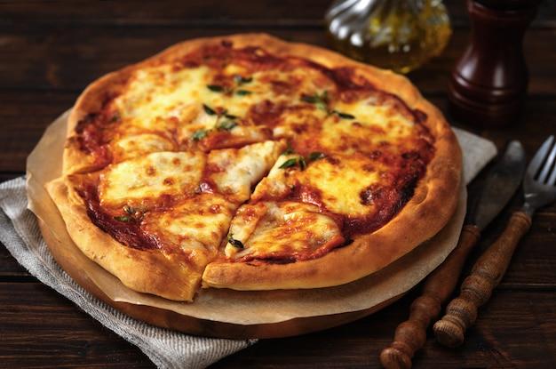 Perto da pizza margherita com uma crosta apetitosa na vista superior do fundo de madeira escuro