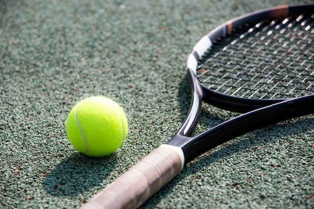 Perto da raquete de tênis e da bola em uma quadra, conceito de esporte