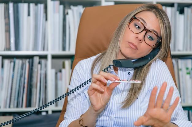 Perto da secretária loira desmotivada, polindo as unhas no local de trabalho enquanto fala ao telefone