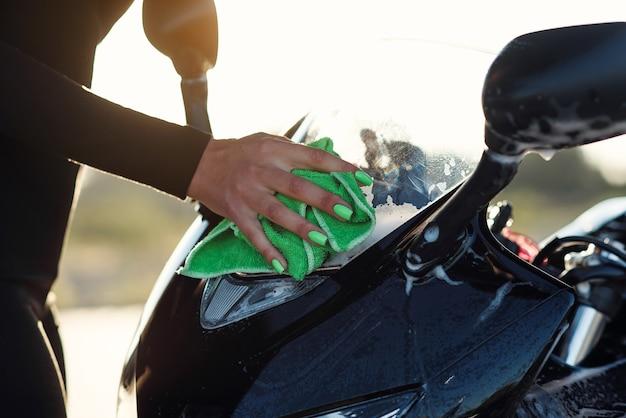 Perto da sedutora jovem lavando as mãos de uma motocicleta esporte elegante e enxugando-a de espuma rosa