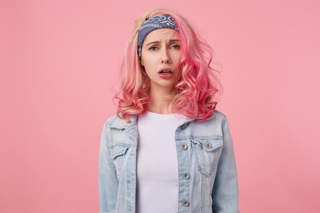 Perto da senhora fofa cansada com cabelo rosa, olhando triste, não consigo encontrar o vestido certo para a próxima festa. de pé, vestindo uma camiseta branca e uma jaqueta jeans.