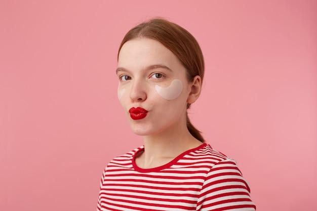 Perto da simpática jovem ruiva sorridente com lábios vermelhos e com manchas sob os olhos, usa uma camiseta listrada vermelha, olha e manda beijo, fica de pé.