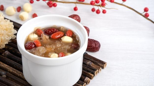 Perto da sopa doce tradicional chinesa de fungo branco de neve com semente de lótus, datas vermelhas (jujuba) e wolfberry (goji, gojiberry).