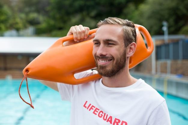 Perto da sorridente salva-vidas carregando uma lata de resgate à beira da piscina