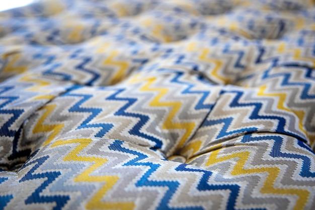 Perto da textura macia do sofá mosqueado com botões afundados. idéia e variante de tecido para estofamento de sofá.