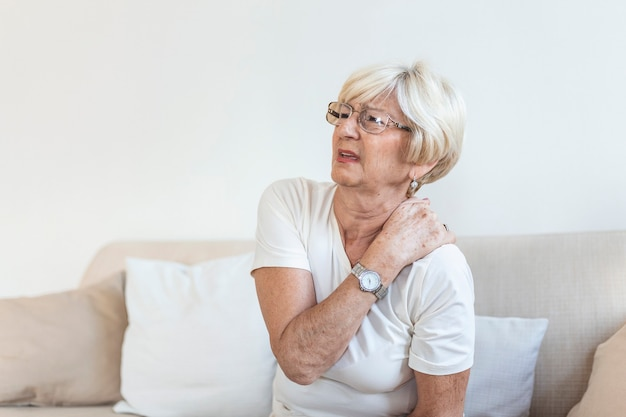Perto da triste senhora sênior com dor no pescoço. mulher idosa com fibromialgia de síndrome de dor crônica, sofrendo de dores de garganta agudas. mulher idosa com dor no pescoço