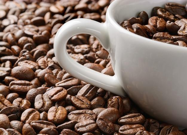 Perto da xícara de café branco em muito fundo de grãos de café. foto macro de grãos de café na xícara