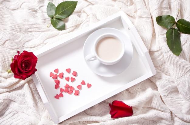 Perto da xícara de chá com rosa vermelha na bandeja branca