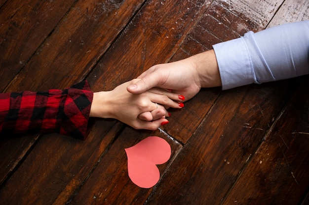 Perto das mãos com corações vermelhos no dia dos namorados