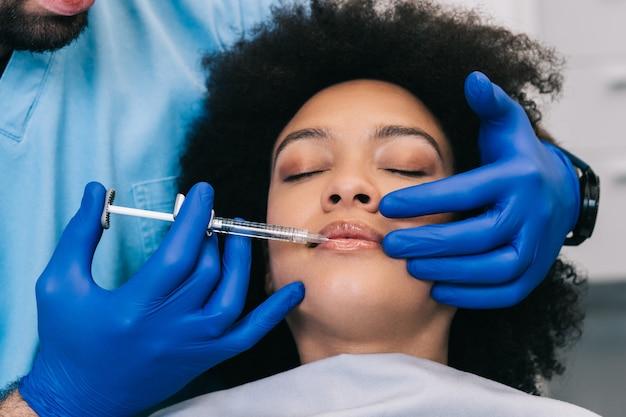 Perto das mãos da especialista em esteticista, injetando botox nos lábios femininos.