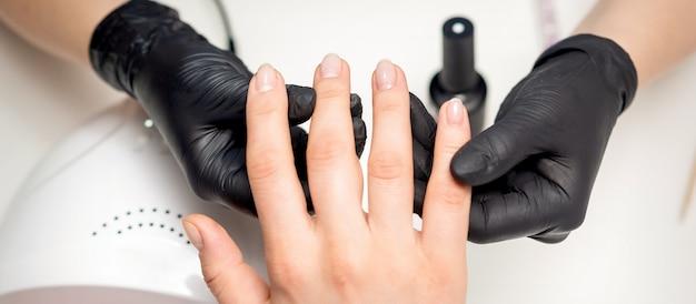 Perto das mãos da manicure em luvas pretas estéreis segurando os dedos da cliente em um salão de manicure