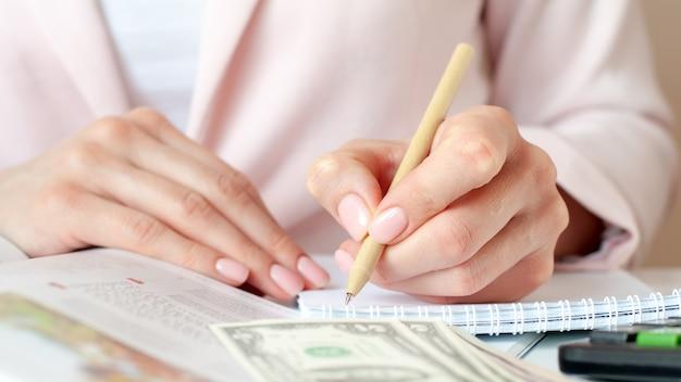 Perto das mãos da mulher com a calculadora contando e fazendo anotações no caderno