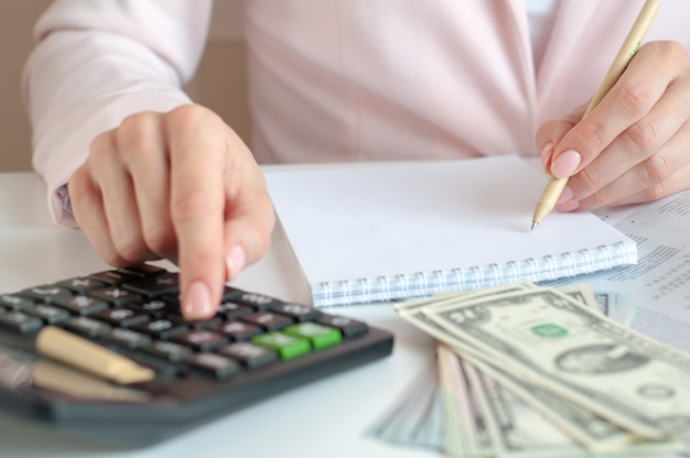 Perto das mãos da mulher com calculadora, contando e fazendo anotações para o caderno. conceito de finanças, economia, tecnologia e pessoas. foco seletivo.