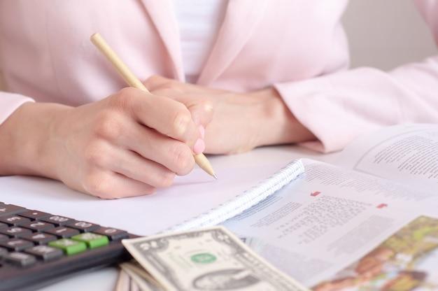 Perto das mãos da mulher com calculadora, contando e fazendo anotações para o caderno.