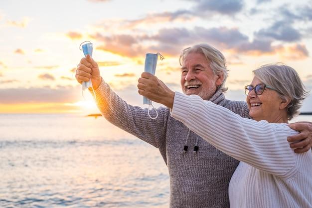 Perto das mãos de duas pessoas abraçadas com suas máscaras para proteger do covid ou do vírus em suas mãos após vencer o coronavírus e ficar livre ao ar livre na praia
