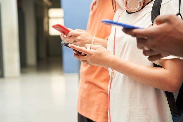 Perto das mãos de um grupo multiétnico de alunos irreconhecíveis usando um smartphone conectado ...