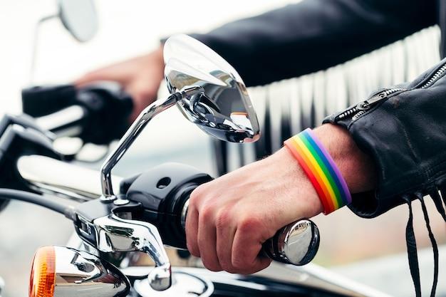 Perto das mãos de um homem com pulseira de arco-íris
