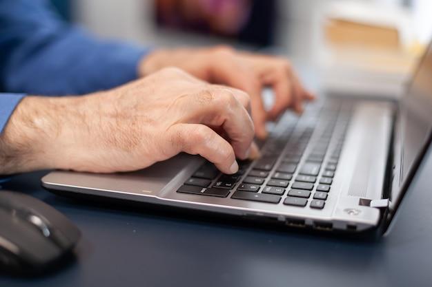 Perto das mãos de um homem sênior, digitando no teclado do laptop