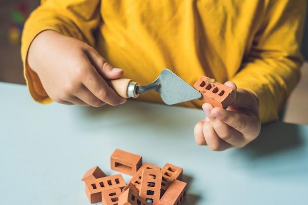 Perto das mãos de uma criança brincando com pequenos tijolos de barro reais na mesa