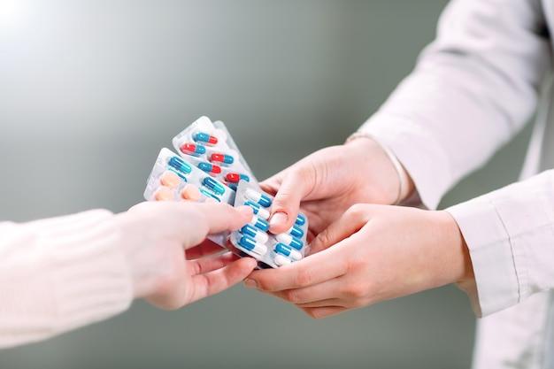 Perto das mãos de uma garota, comprando comprimidos em uma farmácia.