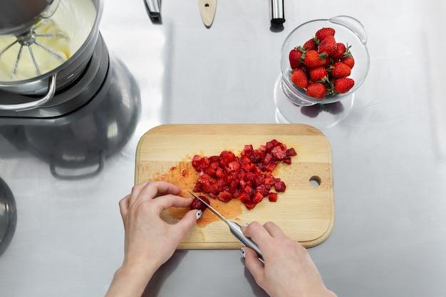 Perto das mãos de uma mulher cortando morangos na tábua