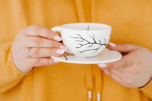 Perto das mãos de uma mulher em um moletom laranja segurando uma caneca de café.
