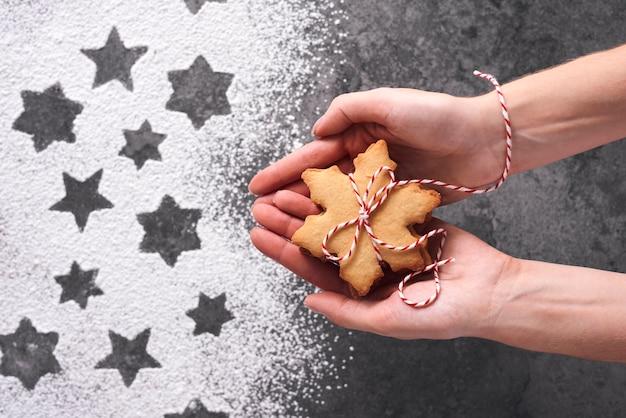 Perto das mãos de uma mulher segurando biscoitos de gengibre