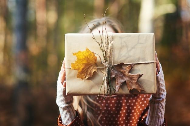 Perto das mãos de uma mulher segurando um presente na floresta de outono