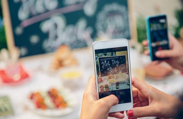 Perto das mãos de uma mulher tirando fotos com o smartphone para a mesa com comida e bebida em uma festa de verão ao ar livre