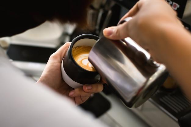 Perto das mãos do barista do café estão fazendo latte art.