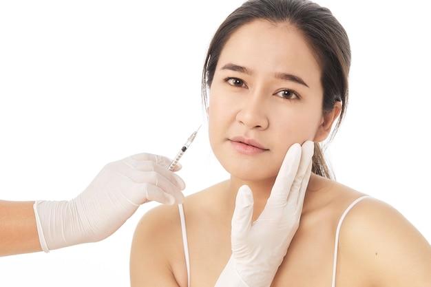 Perto das mãos do cosmetologista fazendo injeção de botox em rosto feminino