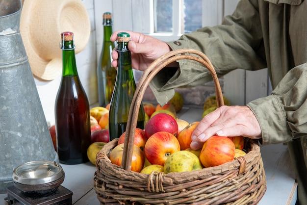 Perto das mãos do homem com uma garrafa de cidra e maçãs