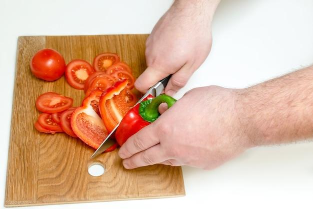 Perto das mãos do homem cortando tomates frescos maduros e pimenta com faca em uma tábua de madeira em uma cozinha em casa.