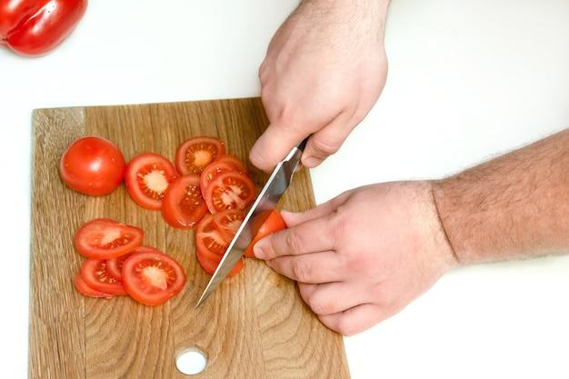 Perto das mãos do homem segurando uma faca e picar tomates frescos maduros em uma tábua de madeira em uma cozinha em casa.