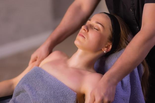 Perto das mãos do massagista massageando o rosto feminino. mulher fechou os olhos com prazer.