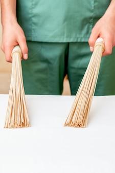 Perto das mãos do massagista segurando vassouras de massagem de bambu em cima da mesa.