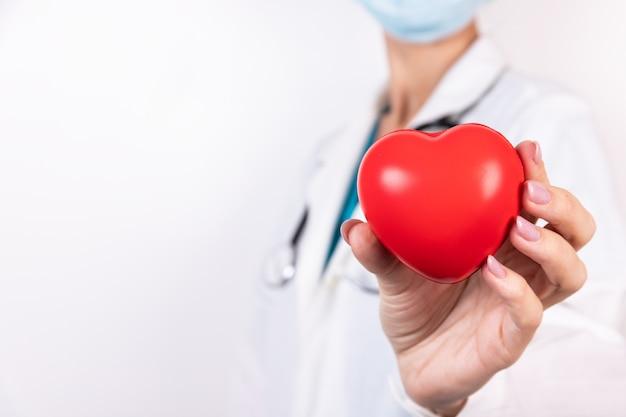Perto das mãos do médico com o coração