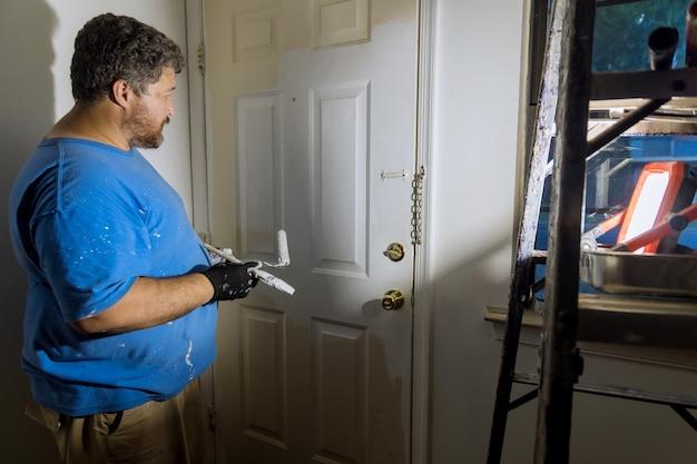 Perto das mãos do pintor com luvas, pintando a moldura da porta usando o rolo de mão na restauração da casa do trabalhador