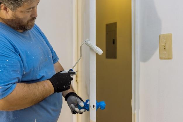 Perto das mãos do pintor com luvas, pintando a moldura da porta usando o rolo de mão