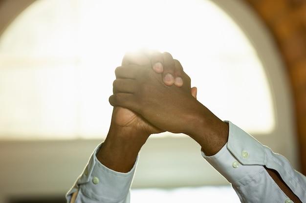 Perto das mãos do ser humano afro-americano e caucasiano unidas. mãos femininas tocando em um gesto de amizade, união, família, trabalho em equipe ou direitos das mulheres, sucesso, mão amiga.