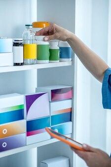 Perto das mãos dos médicos à procura de um frasco de comprimidos