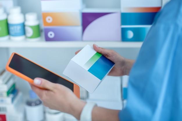 Perto das mãos dos médicos segurando um pacote com comprimidos e tablet