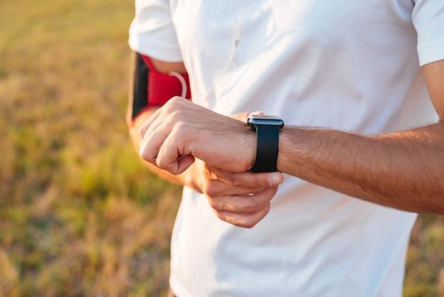 Perto das mãos masculinas esportivas com smartwatch ao ar livre