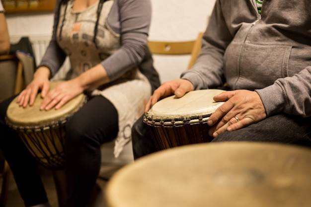 Perto das mãos na bateria africana, tocando bateria para uma musicoterapia
