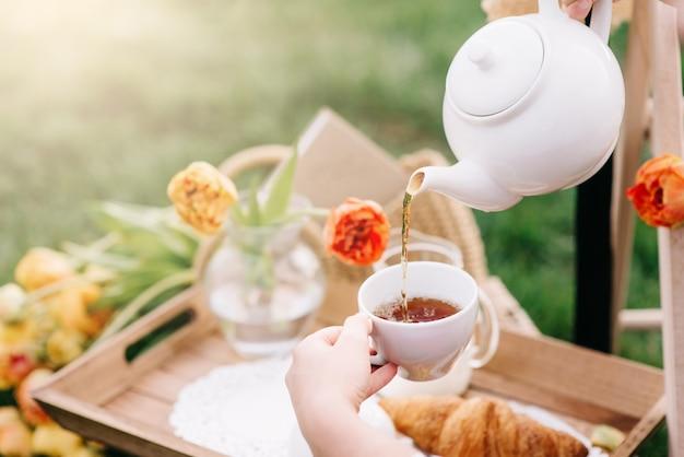 Perto das mãos servindo chá na xícara branca, piquenique no jardim da primavera