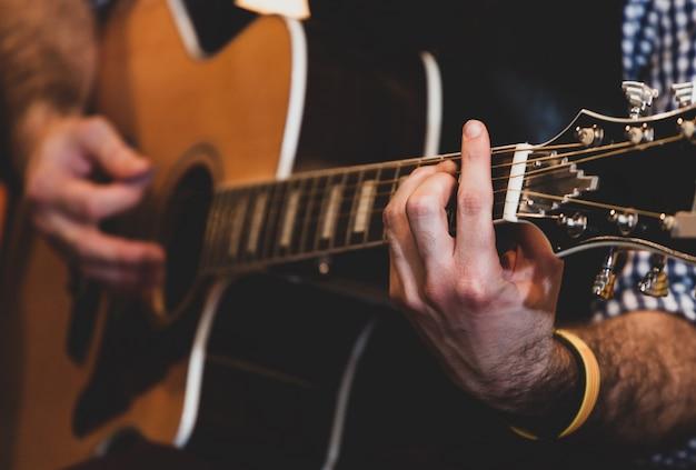 Perto das mãos tocando violão clássico. foco seletivo.