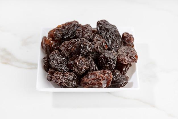 Perto das passas no prato isolado na superfície de mármore branco. uva seca
