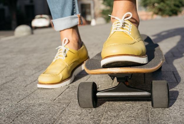 Perto das pernas do homem em sapatos elegantes, andando de skate. conceito de estilo de vida ativo