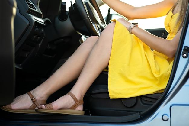 Perto das pernas do motorista jovem com vestido de verão amarelo, sentado atrás do volante, dirigindo um carro.